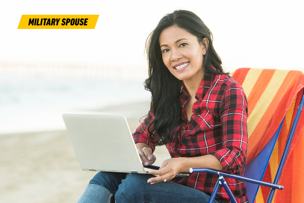 Photo of Chanda sitting on the beach with her laptop