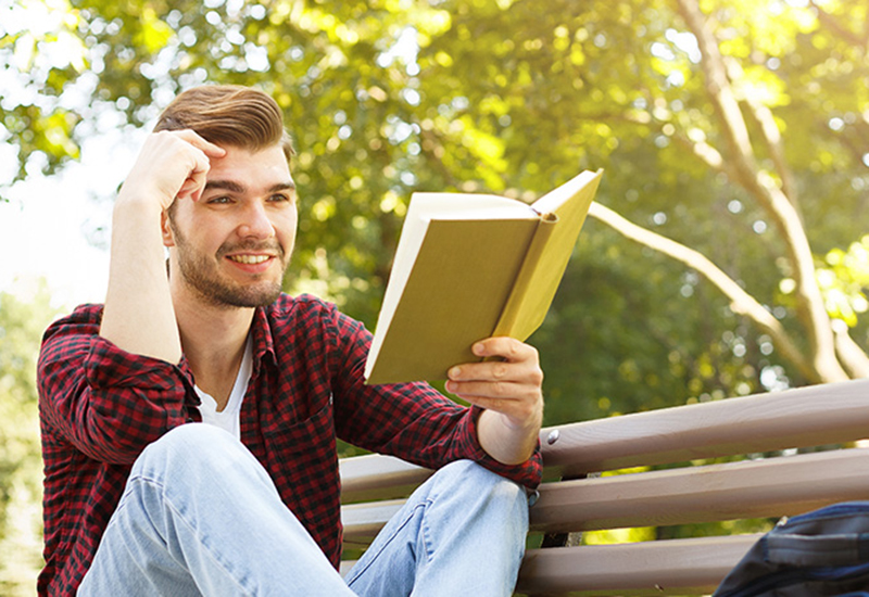 Young male reading a book on a park bench - promoting summer courses