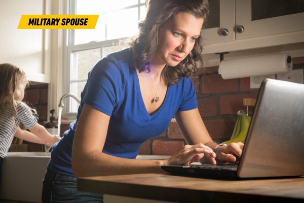 Photo of Amanda in her kitchen, working on her laptop while her daughter is washing her hands at the sink