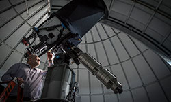 A science professor looking through the telescope in our Academics building