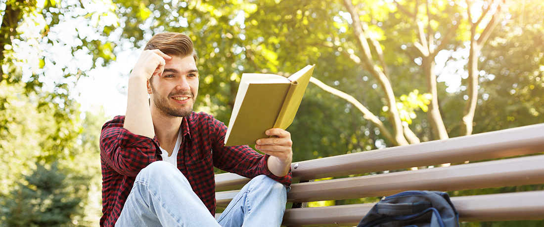 Photo of a young college male reading a book.