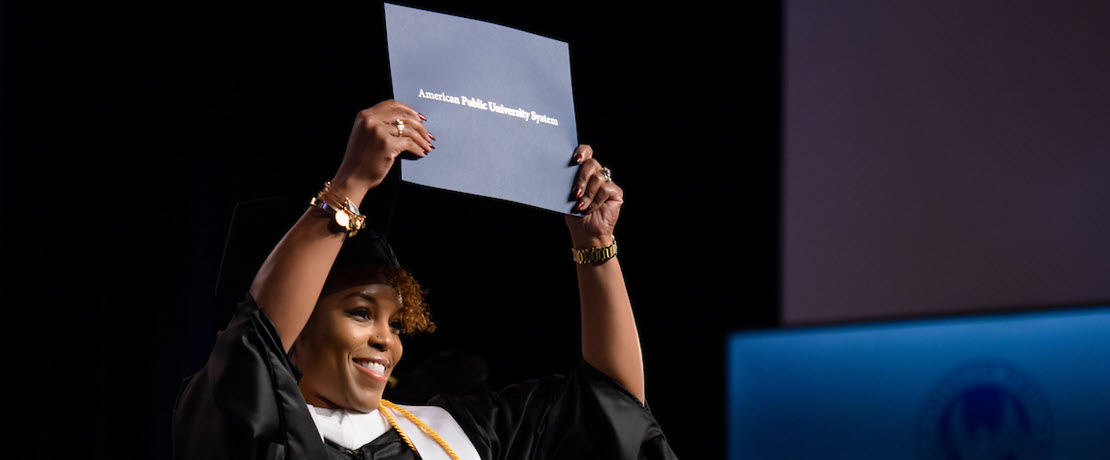 Female alumna holding diploma on Commencement stage.